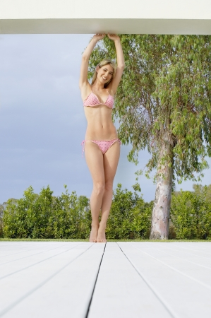 Young Woman in bikini posing on deck front view ground\ view