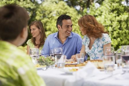 mixed age range: Familia que tiene comida en la mesa en el patio trasero