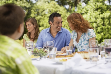 mixed age range: Family having meal at table in back yard LANG_EVOIMAGES