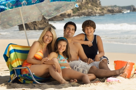 family: Family in swimwear on beach sitting on lounge chair under parasol portrait LANG_EVOIMAGES