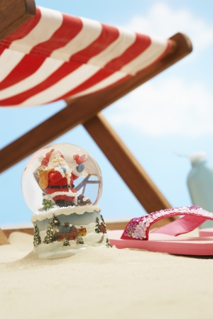 deckchair: Souvenir santa snow globe under deckchair on beach close up