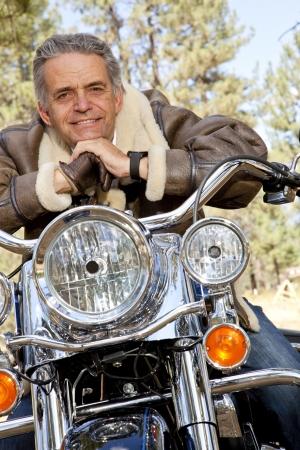 handle bars: El hombre mayor apoyado en el manillar de motocicleta