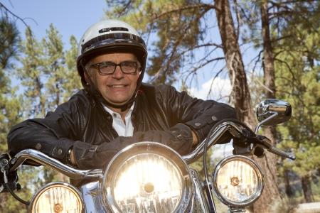 handle bars: El hombre mayor uso del casco apoyado en el manillar de la motocicleta en el bosque
