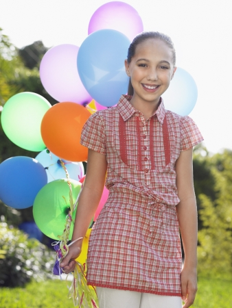 preteen girl: Portrait of girl (10-12) with bunch of balloons smiling