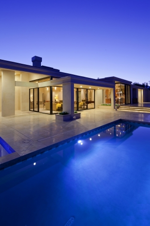 resid: Rear view of luxury villa at night time with swimming pool LANG_EVOIMAGES
