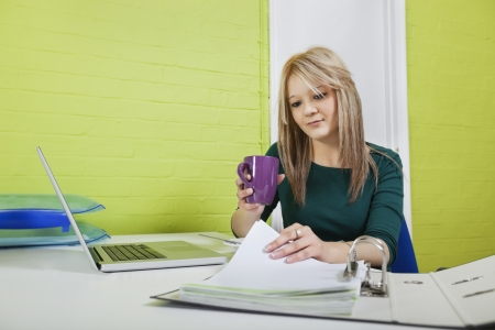 reviewing documents: Young businesswoman with coffee mug reviewing documents at desk LANG_EVOIMAGES