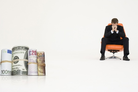 economic issues: Money rolls with worried businessman on chair representing financial problems
