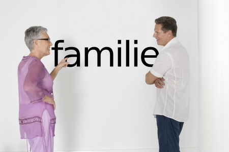 german ethnicity: Couple discussing family issues against white wall with German text Familie