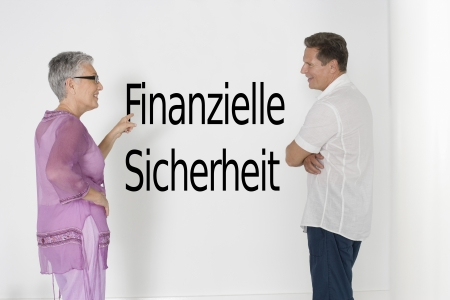 sicherheit: Couple discussing financial security against white wall with German text Finanzielle Sicherheit LANG_EVOIMAGES