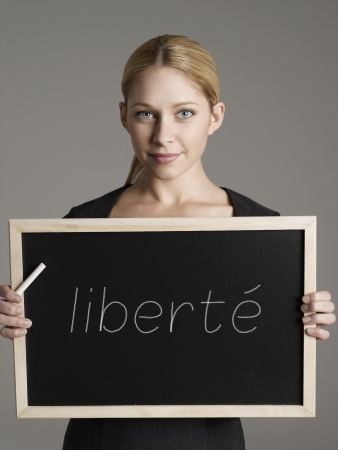 fro: Portrait of young businesswoman holding blackboard with French text liberté (freedom) LANG_EVOIMAGES