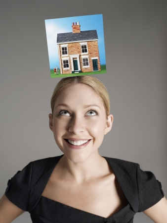homeownership: Model home on top of young womans head representing homeownership