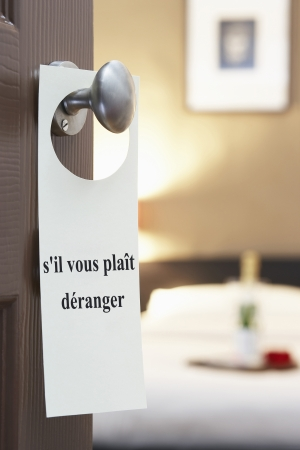 sil: Sign with French text sil vous plait deranger (please disturb) hanging on hotel room door