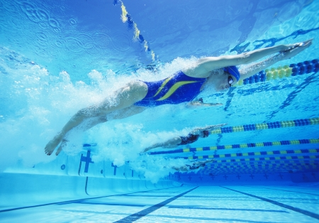 lane marker: Young female professional participants racing in pool LANG_EVOIMAGES