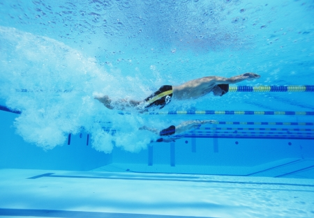 lane marker: Underwater shot of three male athletes racing in swimming pool