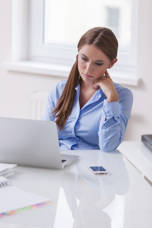 woman serious: Businesswoman looking bored in front of laptop LANG_EVOIMAGES