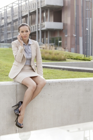 Full length of young businesswoman using mobile phone while sitting on wall against office building Stock Photo