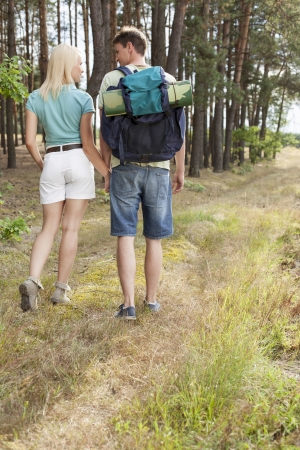 holding hands while walking: Rear view of young hiking couple holding hands while walking in forest LANG_EVOIMAGES