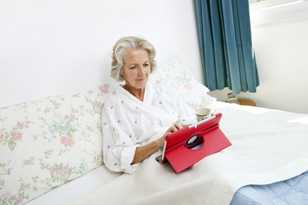 gray haired: Senior woman using digital tablet on bed at home LANG_EVOIMAGES