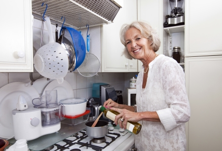 cooking oil: Portrait of senior woman adding olive oil to saucepan at kitchen counter