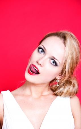 long tongue: Caucasian woman wearing white dress on red background licking her lips