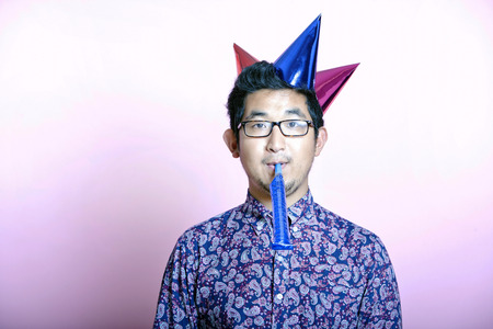 multiple ethnicity: Young Geeky Asian Man wearing many party hats