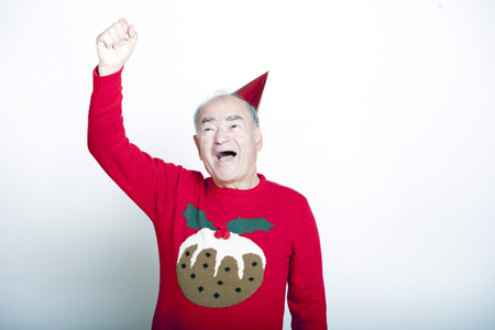 christmas pudding: Senior adult man wearing Christmas jumper raising his arm in the air