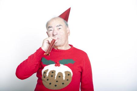 Hombre adulto mayor que desgasta el puente de Navidad que sopla el ventilador del partido Foto de archivo - 23272249