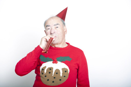 people  camera: Senior adult man wearing Christmas jumper blowing party blower