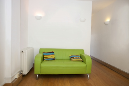 wall sconce: Cushions on green sofa in empty office