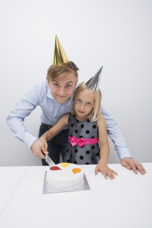 Portrait of father and daughter cutting birthday cake at table Stock Photo - 25344760