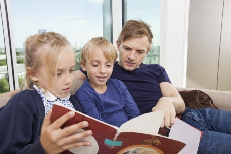 storybook: Father and children reading storybook on sofa at home
