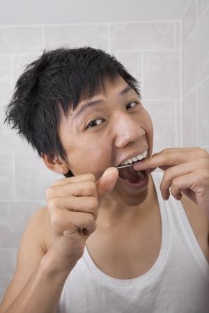 flossing: Portrait of mid adult man flossing his teeth in bathroom