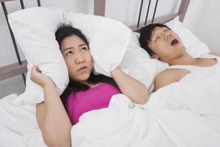 Frustriert Frau, die Ohren mit Kissen, während der Mensch im Bett Schnarchen Standard-Bild