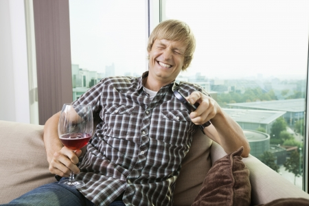 changing channels: Cheerful mid-adult man with wine glass watching television on sofa at home LANG_EVOIMAGES