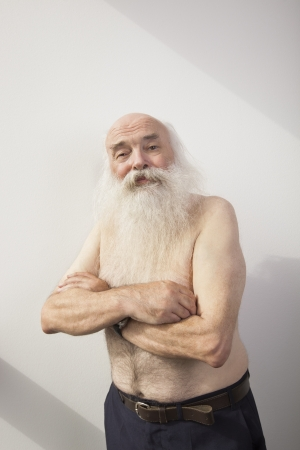 partially nude: Portrait of shirtless senior man with arms crossed over white background