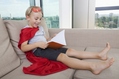 boy barefoot: Happy little boy in superhero costume reading book on sofa at home