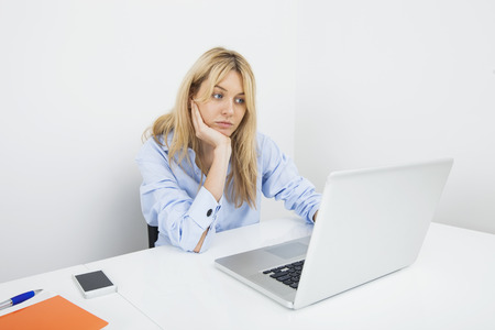 Bored young businesswoman using laptop at desk in office