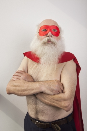 partially nude: Shirtless senior man in super hero costume against white background
