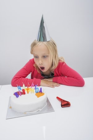 noisemaker: Surprised girl looking at birthday cake on table in house
