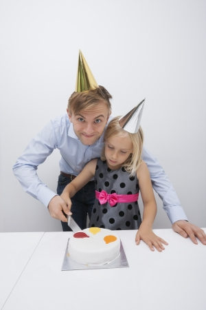 Portrait of smiling father cutting birthday cake with daughter at table Stock Photo - 25294801