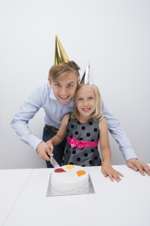 Portrait of happy father and daughter cutting birthday cake at table Stock Photo - 25294802