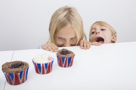 tempted: Tempted children looking at cupcakes on table LANG_EVOIMAGES