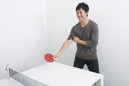 Handsome mid adult man playing table tennis Imagens