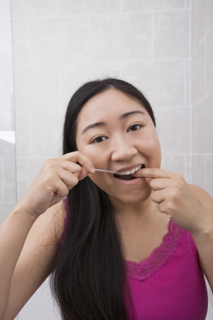 flossing: Portrait of young woman flossing her teeth in bathroom