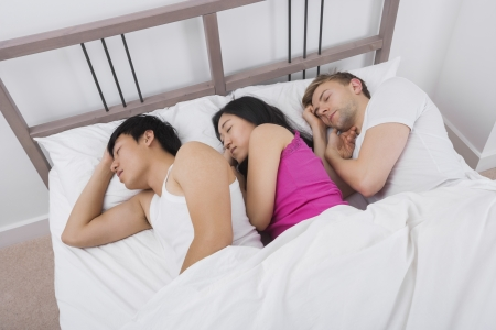 chinese sex: Young woman sleeping with two men in bed LANG_EVOIMAGES