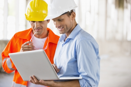 Male architects working on laptop at construction site