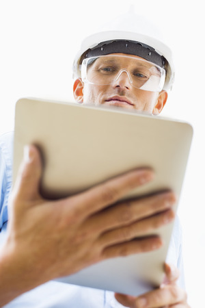Low angle view of male architect using tablet PC against sky Stock Photo - 25345407