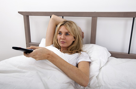 changing channels: Young woman changing channels with remote control in bed LANG_EVOIMAGES