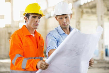 construction site: Male architects analyzing blueprint at construction site