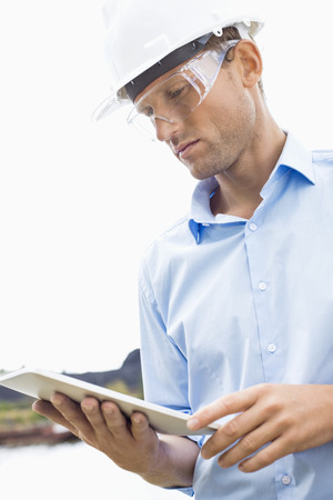 Male architect looking at tablet PC against sky Stock Photo - 25345583